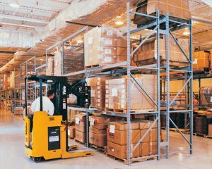 Forklift accessing pallet on racking.